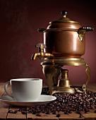 Antike Kaffeemaschine mit dampfender Kaffeetasse und vielen Kaffeebohnen