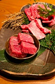 Raw Wagyu beef in a stone bowl and on a stone platter