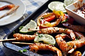 Grilled Shrimp with Toothpicks on a Baking Pan with Lime and Cocktail Sauce