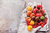 Verschiedene Tomaten und Chilischoten auf einem Tuch