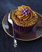A cupcake with a decorative purple flower