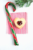 A candy cane and a heart-shaped biscuit with cranberry jam