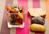 Steamed potatoes and sweet potatoes in a square glass, with raw potatoes to one side