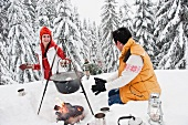 Couple cooking Christmas dinner over campfire in snowy forest