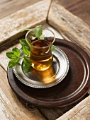 Black tea with fresh mint on a tray