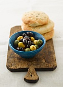 Olives and pita breads on a chopping board