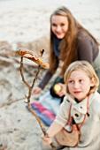 Kinder grillen Würstchen am Strand