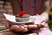 A chocolate cupcake with redcurrants