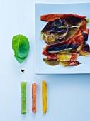 Angebrannte Paprikaschalen, Paprikafruchtfleisch und Basilikumblatt