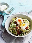 Spaghetti with chicken and ham; a soft-boiled egg on top