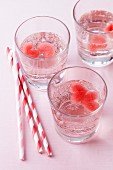 Water in glasses with heart-shaped ice cubes made from fruit juice