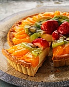 Fruit tart topped with mandarins and strawberries, with one slice cut