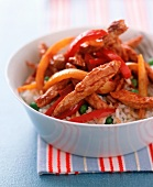 Chicken pieces with peppers on a bed of rice