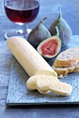 A log of soft cheese with bread and figs