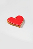 A heart-shaped biscuit with red sugar icing