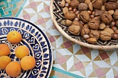 Apricots on a ceramic plate, assorted nuts in a basket