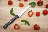 Fresh strawberries, mint leaves and a knife on a wooden board