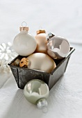 White, gold and silver Christmas tree baubles in a loaf tin