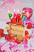 Ein Stück Erdbeertorte mit Kerzen zum Geburtstag