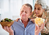 An older couple choosing between salad and crisps