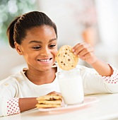 A girl dunking a biscuit in a glass of milk