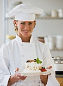 Female chef holding plate of dessert