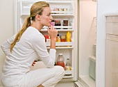 Woman looking inside refrigerator