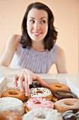 Frau greift nach Doughnut in einer Schachtel