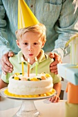 Young child blowing out birthday candles