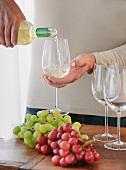 Mann giesst Weisswein in ein Glas
