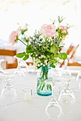 Vase of roses on set dinner table with glasses