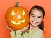 Smiling girl holding a jack o lantern