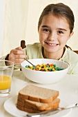 Young girl eating breakfast cereal