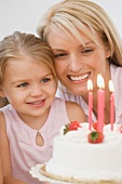 Mother and daughter smiling at birthday cake