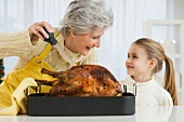 Grandmother and daughter basting roast turkey