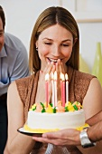Woman smiling at birthday cake