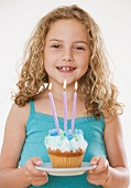 Girl holding cupcake with candles