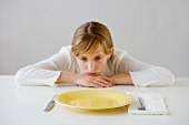 Teenaged girl looking at empty plate