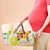 Schwangere Frau hält Einkaufskorb mit Babysachen