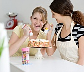 Teenage girls decorating cake