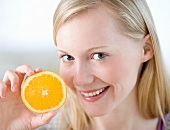 Woman holding half of orange