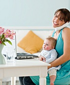 Mother holding baby and working at home
