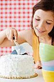 Teenage girl frosting cake