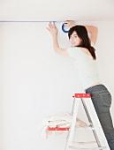 Junge Frau bereitet die Wand für das Streichen vor