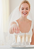 Young bride reaching for glass of champagne