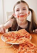 Girl eating spaghetti with tomato sauce