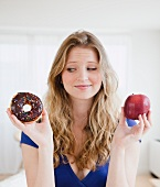 Young woman choosing between donut and apple