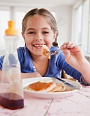Young girl eating pancakes
