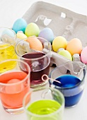 Becher mit Eierfarben und gefärbte Ostereier im Eierkarton