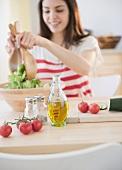 Junge Frau bereitet Salat zu